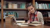 enciclopédia : Smiling caucasian girl studying in library, doing research with pleasure with use of the internet and books, wearing checked casual shirt and glasses on the head, concept of positive attitude to education