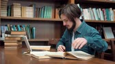 enciclopédia : Hard-working caucasian student studying in library, young man with beard and straight fair hair using laptop while reading book, sitting at brown table next to the bookshelves