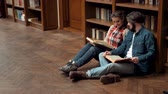 enciclopédia : Two teens reading books while sitting on the floor, looking through the pages attentively, having time off in front of the bookshelves in old library Stock Footage