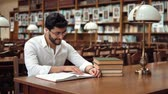 enciclopédia : Good-looking slim man wearing white headphones while reading, smiling student relaxing with book and music at brown wooden table in nice big library Stock Footage