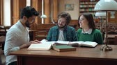 ansiklopedi : Three intelligent students are sitting in big library, chatting about subject while looking through books, beautiful woman wearing green sweater, man near by - denim shirt, black-haired man - white shirt