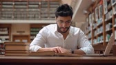 ansiklopedi : Intellectual young man succeeded in finding information, good-looking boy in neat white shirt reading an old book, using laptop to check data on the internent Stok Video