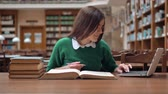 enciclopédia : Bright female student studying in huge library, prettty girl in green sweater and smart white blouse searching information on the internet, using white laptop while reading encyclopedia