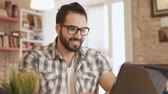 dormitory : Motivated student typing happily on laptop, intellectual boy in round glasses working on the task in comfortable well-furnished dormitory room Stock Footage