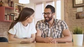 dormitory : Happy friend giving gorgeous smiles while talking, sitting with book and tablet at square brown table, indoor shot at relaxing weekend in modern educational cafe Stock Footage