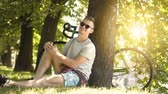 полдень : Joyful teenager in black sunglasses having a rest in gorgeous spring park, sitting on green grass among the trees and enjoying the break after cycling, slowmotion