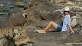 şort : Young attractive woman sunbathing on the rocky coast, watching around and enjoying the sun while having summer vacation Stok Video