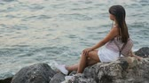 einsamkeit : Tanned slender girl with long hair dreaming as watching the evening sea, concept of summertime calmness Stock Footage
