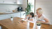 espaçoso : Loving mother helping daughter to draw a picture, good-looking young woman sitting next to fair-haired girl in cozy kitchen