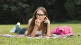 резервный : Smart brunette eating an apple as reading exciting book, listening to lovely music and lying on green grass during summer holidays