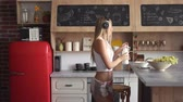 refrigerador : Cute caucasian girl with long straight hair dancing happily as making healthy breakfast, pouring some milk into the bowl on typical weekday morning Stock Footage