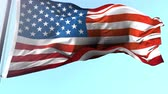 kino : Animation of US flag blowing in the wind in slow motion, American symbol against blue sky