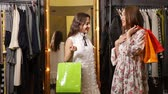 smlouvat : Joyful, slim girls in fashionable dresses talking in the shop, holding bright shopping bags, indoor shot before store mirror
