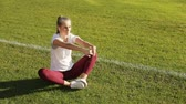 rabo de cavalo : Pretty girl stretching the body as sitting on green pitch grass, doing exercise in the morning before hard working day, concept of sport importance in everyday life