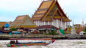 долго : Tourist long-tail boats on the Chao Phraya river, Bangkok, Thailand. Wat Kalayanamit Woramahawihan Buddhist temple compound. Стоковые видеозаписи