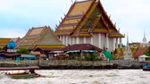 chao phraya : Tourist long-tail boats on the Chao Phraya river, Bangkok, Thailand. Wat Kalayanamit Woramahawihan Buddhist temple compound. Stock Footage