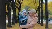 блаженный : Young woman with a baby in her arms. Mom and son are resting in a beautiful autumn park.
