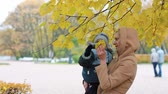 áldás : Young woman with a baby in her arms. Mom and son are resting in a beautiful autumn park.