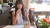tóxico : beautiful brunette smoke electronic cigarette on the summer terrace of restaurant