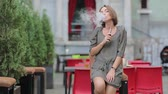 substância : beautiful brunette smoke electronic cigarette on the summer terrace of restaurant