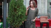fumante : beautiful brunette smoke electronic cigarette on the summer terrace of restaurant