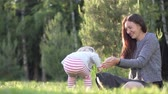 elevação : mom is playing cheerfully in the woods with a little girl. On the street late spring Stock Footage