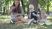 szczęśliwa rodzina : mother with children is drinking tea in the park. They have a bottle and thickets. They pour tea and drink it. Outside summer