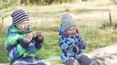 dziecko jedzenie : Brother and sister on a picnic in the autumn forest. Children sit on a log drink a hot hour and eat cookies. They are in jackets and hats. Great video. Cute and beautiful kids