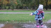 buty : Cute baby jumping on a puddle. On the street autumn, the girl is warmly dressed