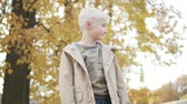 баловать : Handsome blond boy is standing in the autumn park. All trees are in yellow leaves. The boy is dreaming about something. Leaves slowly fall on top of it