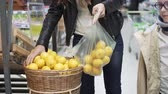 compra : Young beautiful woman packs tangerines in a supermarket. Her son stands next to her and helps her. She takes the orange mandarins from the wooden basket and puts them in a plastic bag. Stock Footage