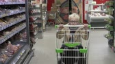 independent : A little boy with glasses is shopping in a grocery store. boy runs forward with a shopping cart in his hands. Slow shooting. Video filmed in the supermarket