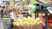 citrom és narancsfélék : Little girl sits in the grocery cart in the supermarket. Next to the baby is a large basket with lemons. The girl takes a lemon and throws them into the basket. She is fun. Funny customer. Little mist