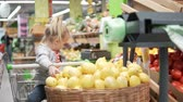 limão : Little girl sits in the grocery cart in the supermarket. Next to the baby is a large basket with lemons. The girl takes a lemon and throws them into the basket. She is fun. Funny customer. Little mist