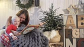 pyžama : Christmas Eve. Mom reads a book to her son. She turns the pages. The apartment is decorated to the new year. The family sits in a comfortable chair, covered with a warm blanket. Nearby is a Christmas Dostupné videozáznamy