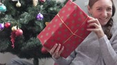 szerény : A young woman is considering her New Years gift. She tries to guess what is hidden under the packaging. The girl is sitting at the Christmas tree and holding a large wrapped gift with a beautiful gol Stock mozgókép
