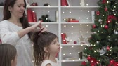 Mom helps daughters braid long hair for the new year. Christmas at home, a woman and her beautiful daughters in dresses near an elegant Christmas tree are doing hairstyles on their long curly hair