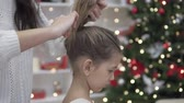 Mom braids hair in the tail of her elegant daughter. Preparing for a great Christmas holiday. A girl in a lush white dress stands with her back to a woman, oa collects her hair with her hands in one t