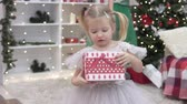 dát : Beautiful elegant woman gives New Years gift to a little girl. Elegant baby takes a box, moves away from the Christmas tree and opens it. She is glad to present. Mom and daughter in Christmas at the