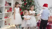 three smart little girls in white dresses are standing by a dressed up Christmas tree. Brother comes up to them and gives children New Years gifts in beautiful packaging. Children rejoice and smile,