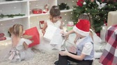 Elegant children sit at the Christmas tree and open beautifully wrapped gifts. Three sisters and brother before the Christmas dinner. In lush evening dresses, the apartment is beautifully decorated fo