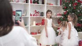 Mom takes pictures of smart daughters at the Christmas tree. Big family is preparing to celebrate Christmas. Fancy girls are standing by the Christmas tree, a woman is making a photo of children on th