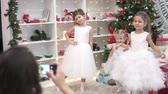 A woman photographs elegant children at the Christmas tree. Cute sisters in lush dresses posing for mom in the Christmas room Wideo
