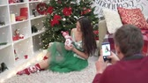 A young woman is sitting by an elegant Christmas tree at home. A man photographing her on a mobile phone. In the hands of the girl toy snowman. Pretty woman smiles and straightens hair