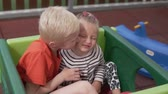 spielplatz : The older brother gently kisses the younger sister on the cheek. Children cute smile and hug each other. Boat and sister play on the playground in the yard