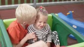 spielplatz : The older brother gently kisses the younger sister on the cheek. Stock Footage