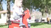 Кипр : Beautiful little girl playing wooden horse in the playground. She swings on the swing and laughs.