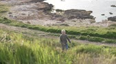 kıbrıs : The boy blond walks in the park by the sea. The child rises up the hill