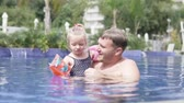 Dad teaches to swim little daughter. A man plays in the pool with a little girl in armbands