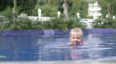 A little girl swims in the pool outside. Holiday at the hotel. The child in the sleeves learns to swim alone. Cute baby is cooled in a bassin on a hot summer day